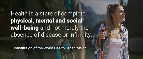 """Image of the quote """"Health is a state of complete physical, mental and social well-being and not merely the absence of disease or infirmity. - Constitution of the World Health Organization"""" over a woman hiking and smiling."""